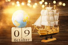 Columbus day concept with old ship over wooden background Stock Photos