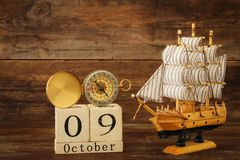 Columbus day concept with old ship over wooden background Royalty Free Stock Photography