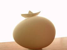 Columbus egg. Egg & paper ship royalty free stock photography