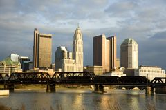 Columbus, Ohio Skyline with Train. Train crosses a bridge over the Scioto River with the skyline of Columbus, Ohio in the background at sunset royalty free stock images