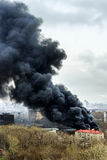 Column of black smoke rising above fireplace in the city Royalty Free Stock Photos