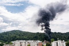 Column of black smoke rising above residential buildings. Stock Photo