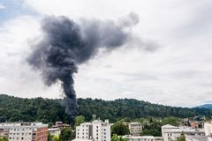 Column of black smoke rising above residential buildings. Column of black smoke rising above a forest nearresidential area Stock Photo