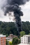 Column of black smoke rising above residential buildings. Stock Photography