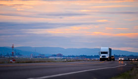 Column of cars led by semi truck on evening winding road Stock Photos