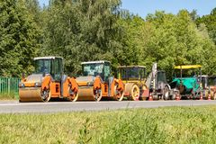 A column of construction equipment stands on the side of the road ready to start repair work on asphalt laying. Moscow, Russia. A column of construction royalty free stock photography