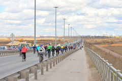 Column of cyclists going down the highway. Royalty Free Stock Images