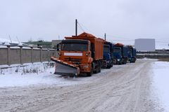 A column of five snow-remover trucks on the road in winter during a snowfall . royalty free stock image