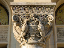 Column head. Column detail, encraved with 2 prey birds protecting a shield (a crest) and sourounded by design details. The column is guarding the entrance of the Royalty Free Stock Images