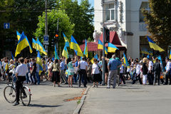 Column of pedestrians with Ukrainian flags. In Dnepropetrovsk, 23 August, celebrate Flag Day. All residents are located on street with yellow-blue flag of Royalty Free Stock Photos