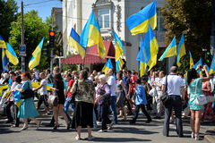 Column of pedestrians with Ukrainian flags. In Dnepropetrovsk, 23 August, celebrate Flag Day. All residents are located on street with yellow-blue flag of Stock Photo