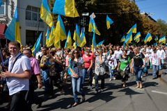 Column of pedestrians with Ukrainian flags. In Dnepropetrovsk, 23 August, celebrate Flag Day. All residents are located on street with yellow-blue flag of Royalty Free Stock Photography