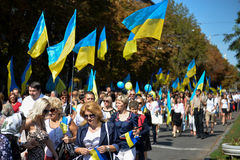 Column of pedestrians with Ukrainian flags. In Dnepropetrovsk, 23 August, celebrate Flag Day. All residents are located on street with yellow-blue flag of Royalty Free Stock Images