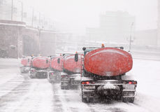 Column of snow-remover trucks on road Royalty Free Stock Images