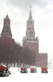 Column of snow-remover trucks on road near Kremlin. Chiming clock of the Spasskaya Tower in Moscow, Russia at wintertime during snowfall Royalty Free Stock Images