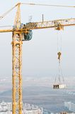 Column tower crane lifting load Stock Images