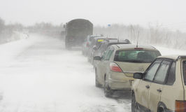 A column of vehicles stuck on the road in a snowstorm stock photography