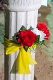 Columna blanca dos con las rosas rojas artificiales y la cinta amarilla imagen de archivo libre de regalías
