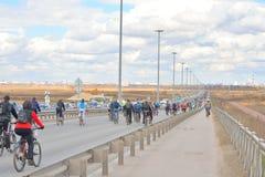Columna de los ciclistas que van abajo de la carretera Fotos de archivo libres de regalías