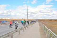 Columna de los ciclistas que van abajo de la carretera Foto de archivo libre de regalías