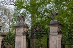 Columna de piedra con las esculturas del águila y puerta del hierro labrado en la entrada a la Universidad de Princeton foto de archivo