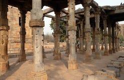 Columnas con la piedra que talla en el patio de la mezquita del Quwwat-UL-Islam, complejo de Qutab Minar, Delhi foto de archivo libre de regalías
