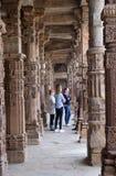 Columnas con la piedra que talla en el patio de la mezquita del Quwwat-UL-Islam, complejo de Qutab Minar, Delhi imágenes de archivo libres de regalías
