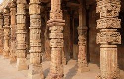 Columnas con la piedra que talla en el patio de la mezquita del Quwwat-UL-Islam, complejo de Qutab Minar, Delhi fotos de archivo libres de regalías