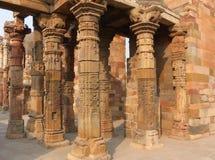 Columnas con la piedra que talla en el patio del mosqu del Quwwat-UL-Islam imágenes de archivo libres de regalías