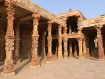 Columnas con la piedra que talla en el patio del mosqu del Quwwat-UL-Islam imagenes de archivo