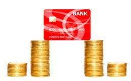 Columnas de las monedas de oro y de la tarjeta de crédito roja aisladas en blanco Imágenes de archivo libres de regalías