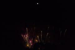 Columnas de oro de fuegos artificiales debajo de una Luna Llena brillante Imagen de archivo