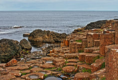 Columnas hexagonales del basalto del terraplén de Giants que llevan abajo en el mar Foto de archivo