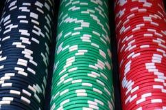 Columnas rojas, azules, verdes, blancas y negras de las fichas de póker Imagenes de archivo