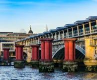 Columnas rojas en el agua contra la perspectiva de un puente en L Imagenes de archivo