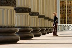 Columns. View of the columns and woman looking to top of front basilique facade royalty free stock photo