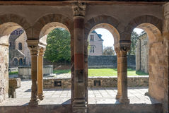 Columns with arches. With garden at the back in Conques France on a sunny day Royalty Free Stock Images