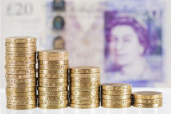 Columns of British Pound Sterling coins in decreasing heights Stock Photo