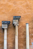 Columns and capitals. In front of a wall painted ocher Stock Image