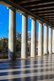 Columns cast shadows across the marble floor of the covered walkway at the restored 2nd century BC Stoa of Attalos in the ancient. Classic Columns cast shadows Royalty Free Stock Photography