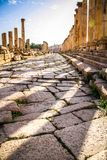 Columns and cobblestones of an ancient Roman road in Jerash royalty free stock image