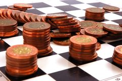 Columns of coins on the chessboard Stock Photo