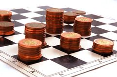 Columns of coins on the chessboard. Columns of  coins on the chessboard isolated on the white background Royalty Free Stock Image