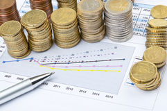 Columns of coins and pen on business chart Royalty Free Stock Photos