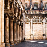 The columns of the Duke's Palace in Dubrovnik. The columns of the Duke's Palace (Knezev dvor) in Dubrovnik, Croatia with Cathedral of the Assumption of the Royalty Free Stock Image