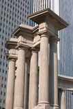 Columns in front of skyscraper. Roman columns in front of highrise building in city stock images