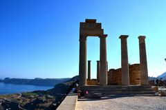 Columns on the hellenistic stoa of the Acropolis of Lindos, Rhodes, Greece, Blue sky, olive tree and beatiful sea view in the back. Ground Stock Photography