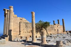 Columns on the hellenistic stoa of the Acropolis of Lindos, Rhodes, Greece, Blue sky, olive tree and beatiful sea view in the back. Ground Royalty Free Stock Photo