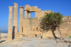 Columns on the hellenistic stoa of the Acropolis of Lindos, Rhodes, Greece, Blue sky, olive tree and beatiful sea view in the back Stock Photo