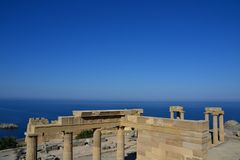 Columns on the hellenistic stoa of the Acropolis of Lindos, Rhodes, Greece, Blue sky, olive tree and beatiful sea view in the back. Ground Royalty Free Stock Image